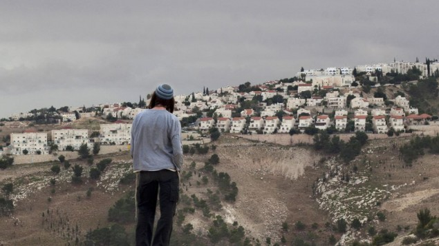 A Jewish settler looks at the West bank settlement of Maaleh Adumim, from the E-1 area on the eastern outskirts of Jerusalem. (photo credit: AP/Sebastian Scheiner)