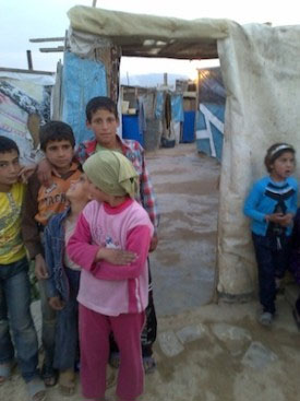 Children gather in front of their makeshift home at a camp in the Beqaa valley
